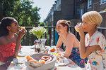 Young women friends enjoying brunch on sunny apartment balcony