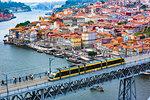 Train on the Dom Luis I Bridge and harbor with the Arrabida Bridge in the distance in Porto, Norte, Portugal