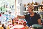 Mature female employee arranging jars in deli