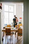 Young man carrying daughter seen through doorway at home