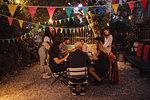 Multi-ethnic friends having dinner during garden party in backyard