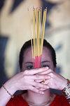 Vietnamese woman in red traditional long dress Ao Dai praying with incense sticks, The Jade Emperor Pagoda, Ho Chi Minh City (Saigon), Vietnam, Indochina, Southeast Asia, Asia