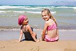 Two girls sitting on beach looking back, portrait, Castellammare del Golfo, Sicily, Italy