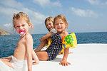 Three cute girls sitting on boat, portrait, Castellammare del Golfo, Sicily, Italy