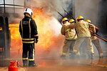 Firemen training, firemen spraying water at fire at training facility, rear view