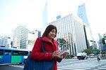 Businesswoman using smartphone in city, Seoul, South Korea