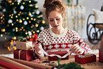 Woman tying ribbon on Christmas present