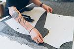 Fashion designer laying out dressmaker's pattern