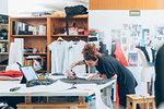 Fashion designer cutting fabric from dressmaker's pattern