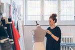 Fashion designer pinning garment onto dressmaker's dummy