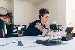 Fashion designer researching using digital tablet