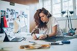 Fashion designer pinning fabric cutouts