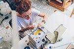 Fashion designer working at sewing machine