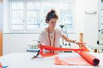 Fashion designer unrolling textile on workbench