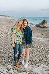 Two young women hugging on beach, Menemsha, Martha's Vineyard, Massachusetts, USA