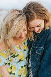Two young women hugging on beach, close up, Menemsha, Martha's Vineyard, Massachusetts, USA