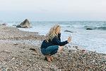Young woman crouching on beach looking at smartphone, Menemsha, Martha's Vineyard, Massachusetts, USA