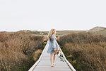 Young woman carrying bunch of flowers on coastal dune boardwalk,  Menemsha, Martha's Vineyard, Massachusetts, USA