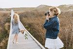 Young woman photographing friend on coastal dune boardwalk,  Menemsha, Martha's Vineyard, Massachusetts, USA