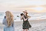 Young woman photographing friend on windy beach,  Menemsha, Martha's Vineyard, Massachusetts, USA