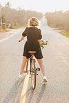 Young woman riding bicycle on rural road, rear view, Menemsha, Martha's Vineyard, Massachusetts, USA