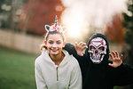 Siblings in halloween costume posing in park