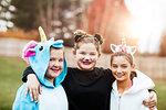 Girls in halloween costume posing in park