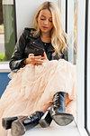 Woman Sitting in Shop Window Sill  Using Smartphone