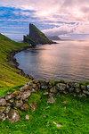 Sunset on the calm ocean and Drangarnir rock, Vagar island, Faroe Islands, Denmark, Europe