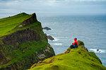 Man sitting on cliffs looks towards the lighthouse, Mykines island, Faroe Islands, Denmark, Europe