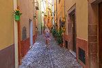 A girl walks in a street of Bosa, Oristano province, Sardinia, Italy, Mediterranean, Europe