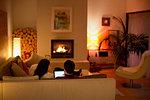 Couple using digital tablet on living room sofa facing fireplace