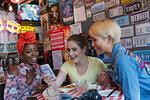 Young women friends using smart phone in bar
