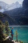 Female hiker looking at sunny, idyllic mountain lake view, Yoho Park, British Columbia, Canada