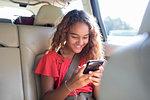 Tween girl using smart phone in back seat of car