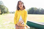 Girl with teddy bear in sunny field with canoe