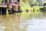 Family dangling feet off sunny riverside dock