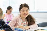 Portrait confident junior high school girl student doing homework in classroom
