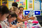 Junior high school girl students using digital tablet in classroom