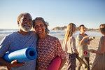 Portrait happy senior couple with yoga mats on sunny beach during yoga retreat