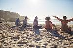 Group sitting on yoga mats on sunny beach during yoga retreat