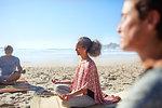 Serene senior woman meditating on sunny beach during yoga retreat
