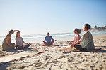 Group meditating on sunny beach during yoga retreat