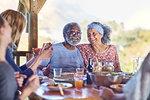 Happy senior couple enjoying healthy meal in hut during yoga retreat