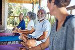 Senior man talking with woman in hut during yoga retreat