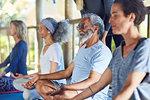 Serene senior man meditating during yoga retreat