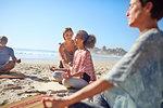 Serene women meditating on sunny beach during yoga retreat