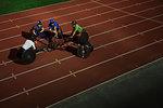 Paraplegic athletes huddling on sports track, training for wheelchair race