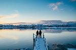 Couple holding hands at the edge of snowy dock overlooking waterfront village, Reine, Lofoten Islands, Norway