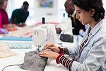 Focused female fashion designer using sewing machine
